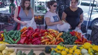 Shoppers buy vegetables at a local Farmers Market in Annandale, Virginia, 8 August 2013
