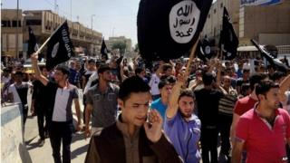 People chant pro-Islamic State group slogans as they carry the group's flags in Mosul in 2014