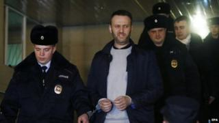 Anti-corruption blogger and liberal opposition leader Alexei Navalny (centre) is escorted into a police car outside Presnensky District Court, in Moscow (19 February 2015)