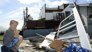A boy sits in front of his family's damaged house in Yeppoon, Queensland. Photo: 21 February 2015