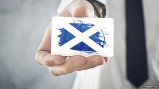 Businessman holding card with saltire