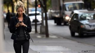 woman using her phone in the street
