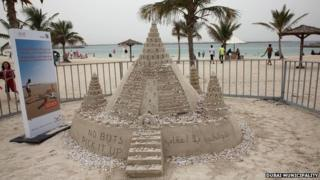 The sandcastle covered in cigarette butts