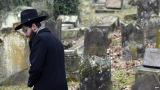 A member of the Jewish community looks at broken tombstones after a ceremony at the Jewish cemetery in Sarre-Union, eastern France, on February 17, 2015, following the desecration of around 300 tombs