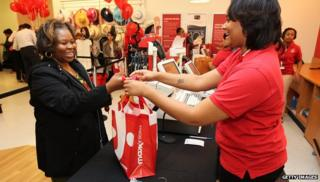 TJ Maxx associate giving shopping bag to customer