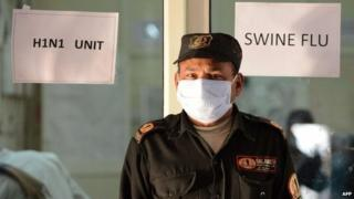An Indian security guard keeps vigil at a swine flu (H1N1) isolation ward of the Ahmedabad Civil Hospital in Ahmedabad on February 3, 2015.