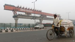 Indian tricycle rickshaw puller passes by an under construction elevated Delhi Metro section in New Delhi.