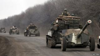 Members of the Ukrainian armed forces ride armoured personnel carriers as they pull back from Debaltseve region, near Artemivsk