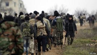 Fighters from Suqour al-Sham Brigade, which is part of the Free Syrian Army, walk with their weapons