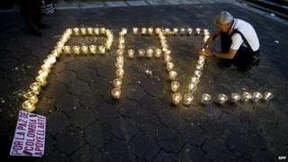 """A man lights candles that read out """"paz"""" [peace]"""