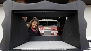Monica Kelsey, a fire-fighter and medic who is president of Safe Haven Baby Boxes Inc., poses with a prototype of a baby box in Woodburn, Indiana