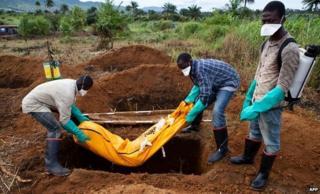 Volunteers bury an Ebola victim in Waterloo, southeast of Freetown - 7 October 2014