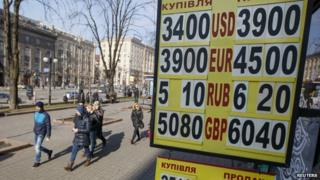 People walk past a board showing currency exchange rates in central Kiev 25 February 2015