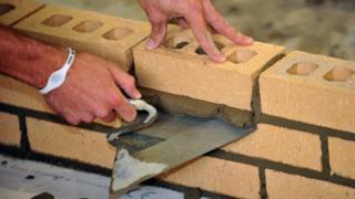 Apprentice bricklayer laying bricks