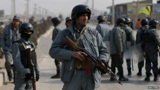 Afghan policemen keep watch at the site of clashes with protesters in Kabul, 31 January 2015