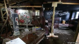 A pint glass and change on the bar; a Tennants tap. View of stage 'Rock the Clutha' backdrop