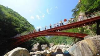 This photo taken on August 31, 2011 shows Chinese tourists admiring the view from a bridge along a path of a scenic spot at the Mount Kumgang international tourist zone in North Korea.