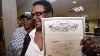 Olanda Smith, left, and Dinah McCaryer show off their certificate after being the first to be married at the Jefferson county courthouse on 9 February