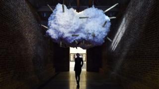 A woman walks below an artwork at the Serpentine Sackler Gallery in London