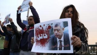 """A protester holds a poster of Interior Minister Mohamed Ibrahim with the word """"Killer"""" on it during a silent protest over a bridge in Cairo, 14 February 2015."""
