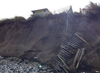 A broken fence shows the extent of storm damage at Whiterocks beach, along Northern Ireland's north coast