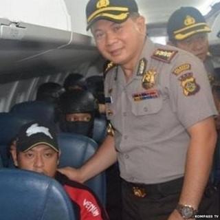 Indonesian policeman Djoko Hari Utomo poses smiling with Andrew Cha
