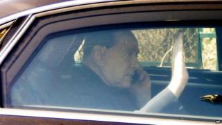 Italy's former PM Silvio Berlusconi on a mobile phone as he leaves the Sacra Famiglia institute in Cesano Boscone, near Milan 06/03/2015