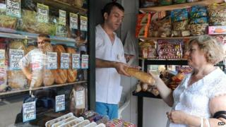 A woman buying bread from a shopkeeper in Russia