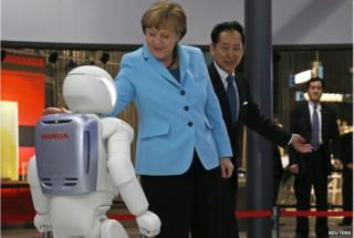 "German Chancellor Angela Merkel (C), escorted by Mamoru Mori, executive director of the museum and former astronaut, touches ""Asimo"", a bi-ped humanoid robot developed by Honda Motor Co., while visiting Miraikan (National Museum of Emerging Science and Innovation) in Tokyo 9 March 2015."