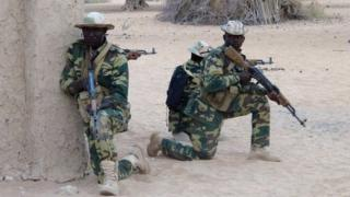 Two Chadian soldiers carrying arms in a desert location