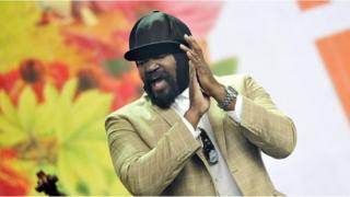 Gregory Porter claps his hands mid-performance