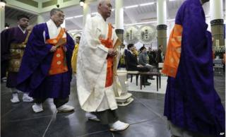 Buddhist priests walk near Japan's Prince Akishino, centre left, and Princess Kiko, centre right, during Tokyo firebombing memorial service in Tokyo Tuesday, 10 March 2015.