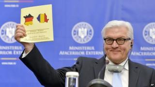 German Foreign Minister Frank-Walter Steinmeier holds up a document celebrating 135-years of German - Romanian diplomatic relations