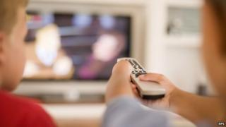 Children watching TV, using a remote control