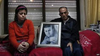The parents of Arab-Israeli Muhammad Said Ismail Musallam sit next to a framed portrait of their son. Photo: February 2015