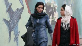 File photo: Two women walk past a mural in the Iranian capital Tehran