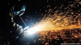 a welder works on a pipe on an oil rig