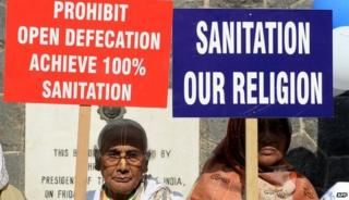 Women holding signs calling for an end to open defecation