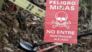 A warning sign is seen as a member of the Humanitarian Demining Battalion of the Columbian Army searches for landmines in Cocorna, Antioquia 3 March 2015
