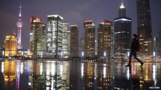 Woman walks at the Bund in front of the financial district of Pudong in Shanghai