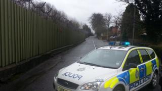 Police car beside barracks fence