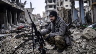 A Kurdish marksman sits in the rubble of the Syrian town of Kobane