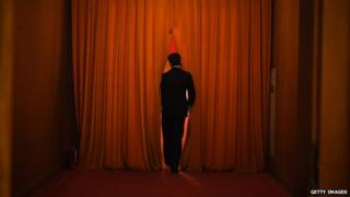 A security guard watches through the curtain during the 3rd plenary session of the third session of the 12th National People's Congress at the Great Hall of the People in Beijing on 12 March, 2015
