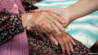 Woman holding an elderly lady's hand