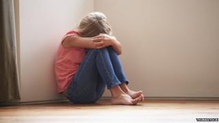A girl sitting in a corner