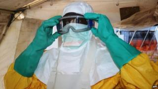 A member of Medecins Sans Frontieres (MSF) or Doctors Without Borders, putting on protective gear at the isolation ward of the Donka Hospital in Conakry 28 June 2014
