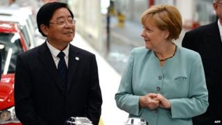 German Chancellor Angela Merkel (R) stands with FAW Group CEO Xu Jianyi