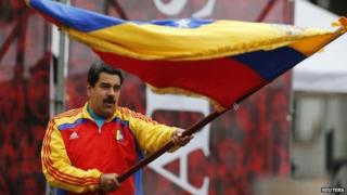 President Nicolas Maduro waves a national flag outside Miraflores Palace in Caracas on 15 March, 2015.