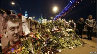 People walk past flowers at the site where Russian politician Boris Nemtsov was killed