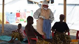 A health worker wearing personal protective equipment assists Ebola patients in the Kenama treatment centre in Sierra Leone - 15 November, 2014